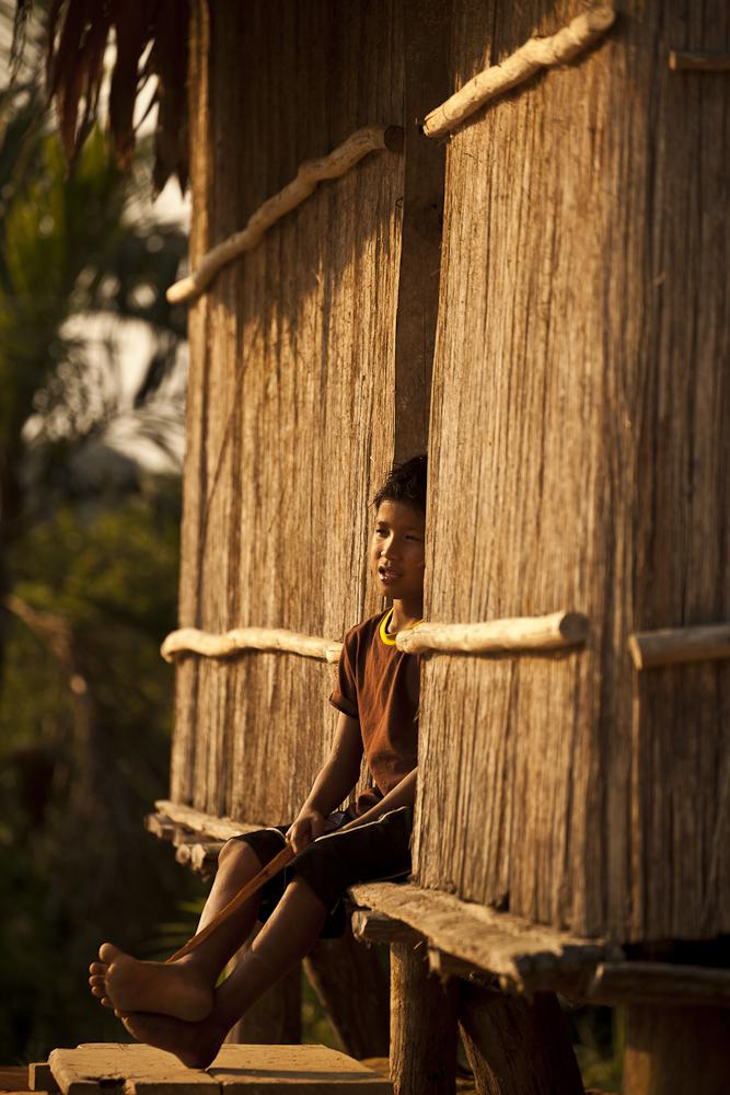 Matsés boy sitting otuside his traditional thatch hut Alicia Fox Photography