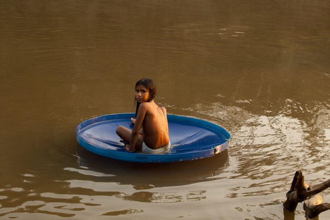 Matsés girl playing on plastic dish in river Alicia Fox