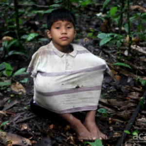 Matsés child protecting himself from mosquitos