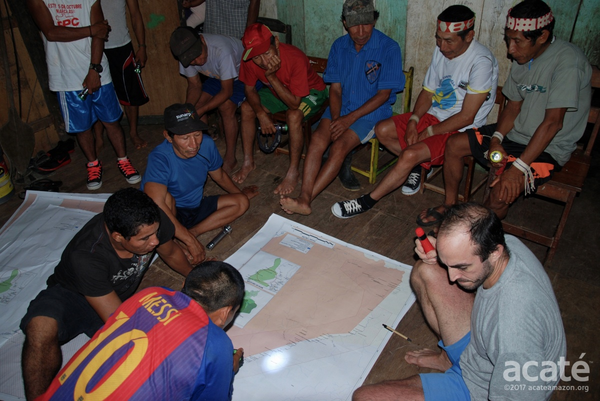 Reviewing the maps at night with the gathered Matsés elders at the meeting©Acaté